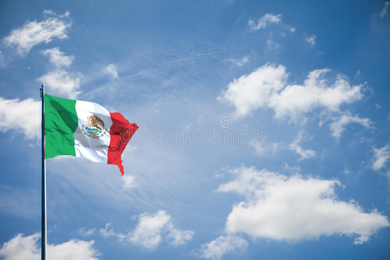 United Mexican States or Estados Unidos Mexicanos nation flag. Is waving on bright blue sky. There are 3 color like green, white and red. And Coat of arms of royalty free stock image