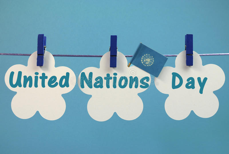United Nations Day greeting message written across white tags with flag hanging from blue pegs on a line stock images