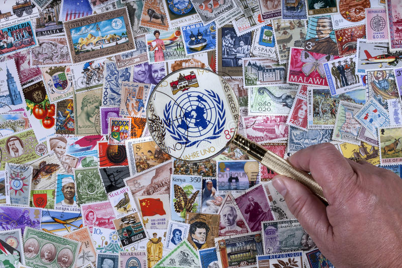 United Nations - Worldwide Postage Stamps. Looking at a postage stamp with the United Nations symbol on it with a magnifying glass over a collection of worldwide stock photo