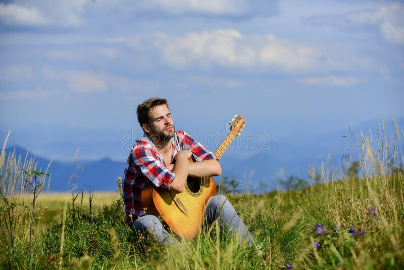 United with nature. Musician looking for inspiration. Dreamy wanderer. Peaceful mood. Guy with guitar contemplate nature. Wanderlust concept. Inspiring nature royalty free stock photo