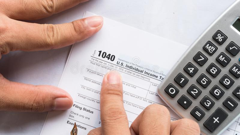 United state 1040 individual tax return form with pen. Hand and calculator thinking about the money for pay to goverment royalty free stock photos