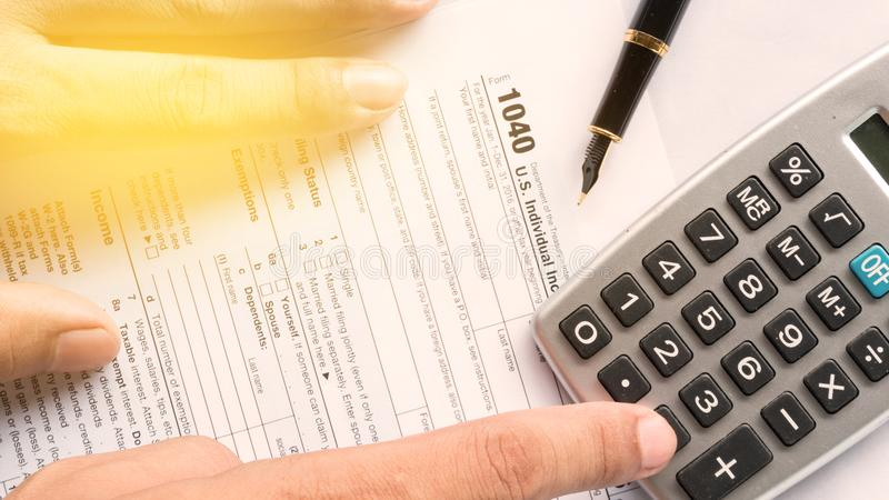 United state 1040 individual tax return form with pen. Hand and calculator thinking about the money for pay to goverment stock photography