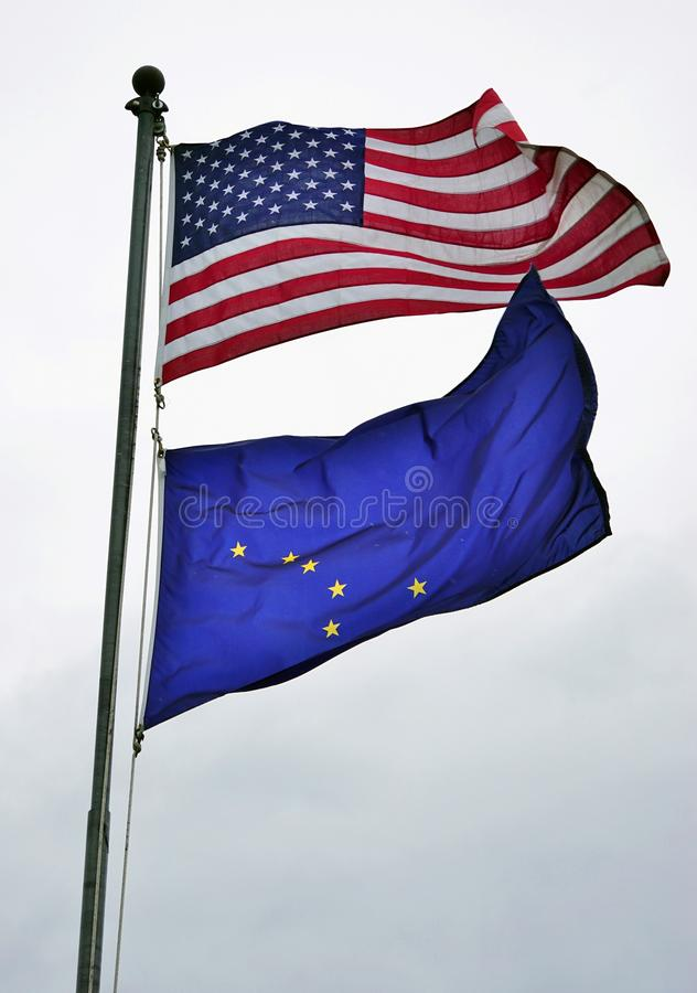 The United States and Alaska flags. ANCHORAGE, AK - A flag of the United States and of Alaska (AK) flying on a mast. Alaska became the 49th state of the United royalty free stock image