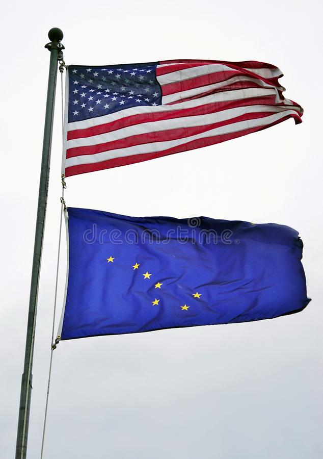 The United States and Alaska flags. ANCHORAGE, AK - A flag of the United States and of Alaska (AK) flying on a mast. Alaska became the 49th state of the United stock photography