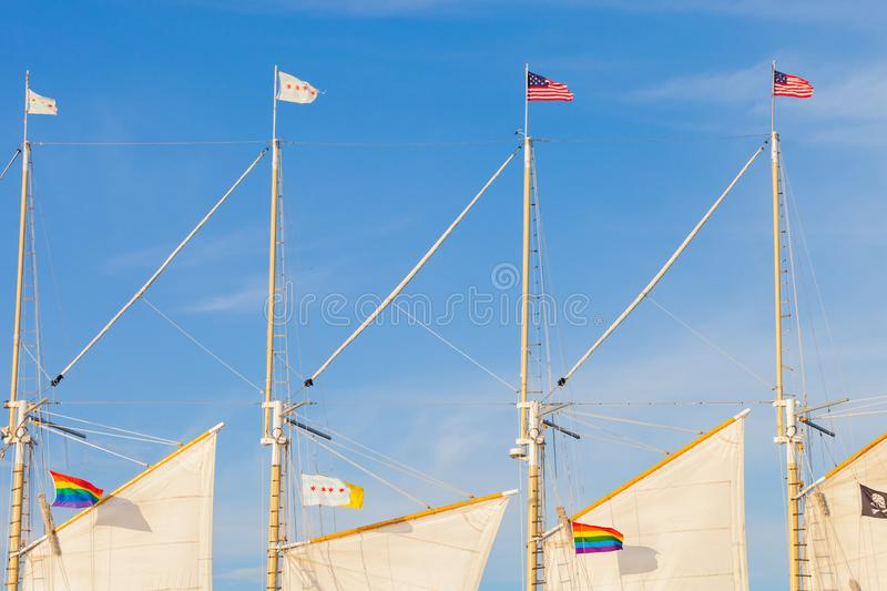The United States of America flag, the city of Chicago flag and. The Rainbow flag flying on the masts of a sailing vessel stock photography