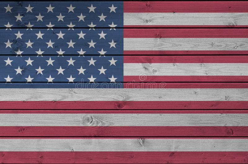 United States of America flag depicted in bright paint colors on old wooden wall. Textured banner on rough background. United States of America flag depicted in royalty free stock image