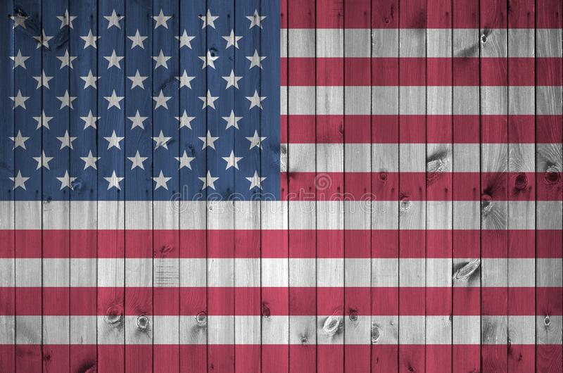 United States of America flag depicted in bright paint colors on old wooden wall. Textured banner on rough background. United States of America flag depicted in royalty free stock photography