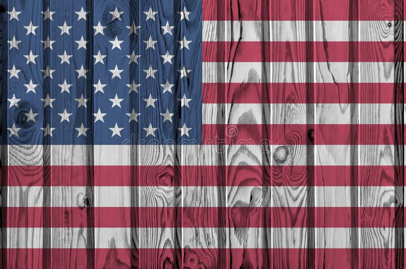 United States of America flag depicted in bright paint colors on old wooden wall. Textured banner on rough background. United States of America flag depicted in royalty free stock photos