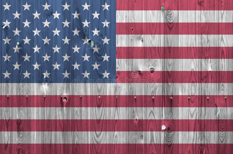 United States of America flag depicted in bright paint colors on old wooden wall. Textured banner on rough background. United States of America flag depicted in royalty free stock photo