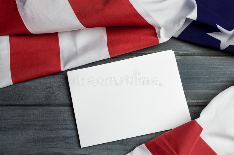 United States of America flag with empty space to write your text on sheet of paper on wooden background.  stock photo