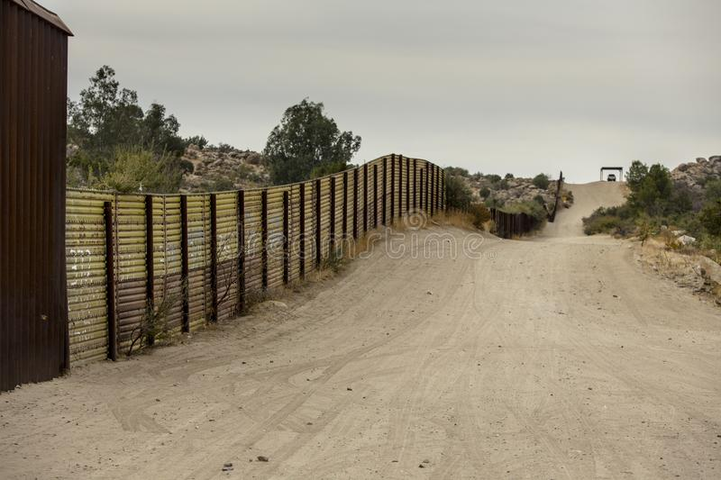 United States Border Wall with Mexico. Jacumba, CA - NOVEMBER 27: United States international wall with Mexico and Border Patrol vehicle in the distance on royalty free stock photography