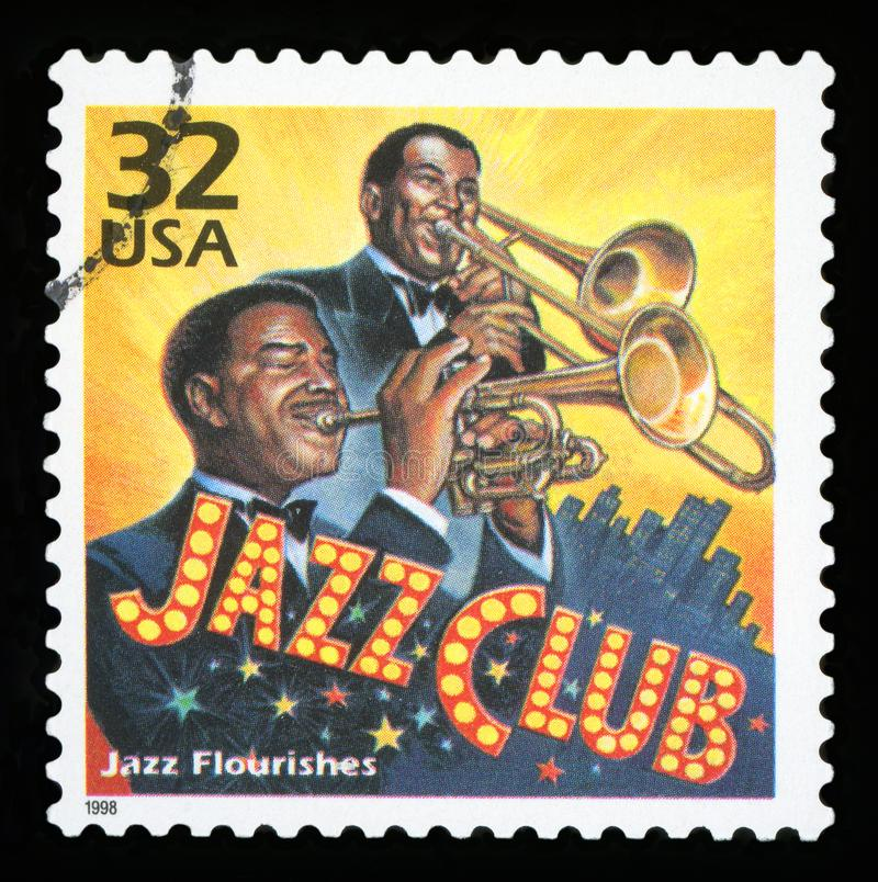 US Postage stamp. UNITED STATES - CIRCA 1998: a postage stamp printed in USA showing an image of jazz musicians playing in a club, circa 1998 royalty free stock photos