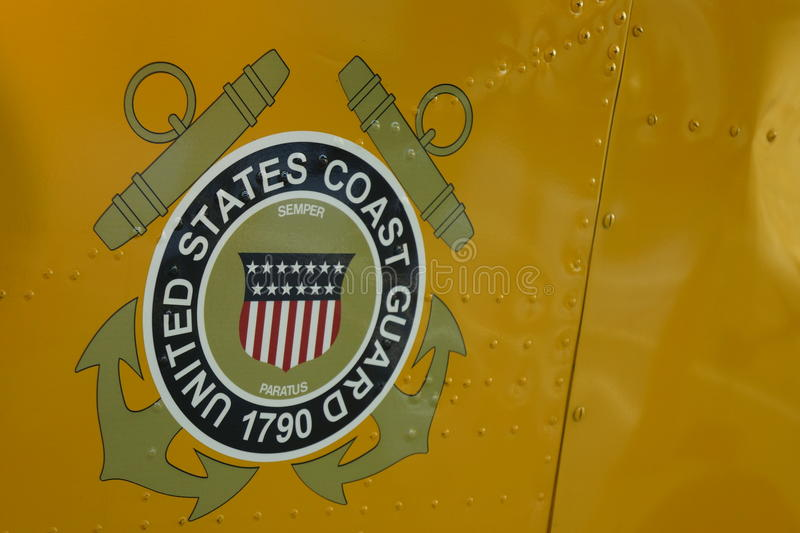 United States Coast Guard logo on military helicopter. United States Coast Guard logo on yellow military rescue helicopter. The USCG protects American coastal stock photos