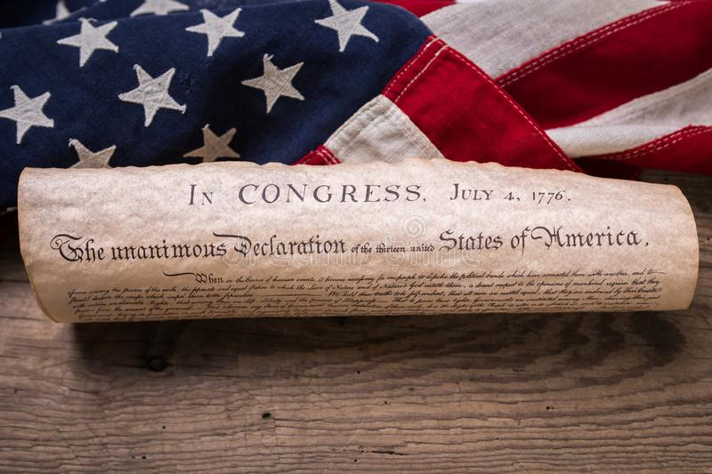 Declaration of Independence. United States Declaration of Independence rolled in a scroll on a vintage American flag and rustic wooden board stock photos