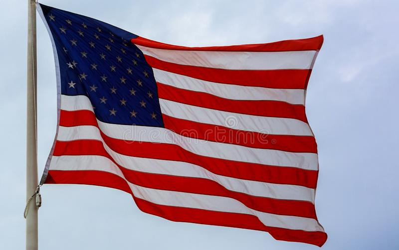 United States flag blows in the wind against a sky. In the blows United States flag wind against asky american day usa independence national waving memorial royalty free stock images