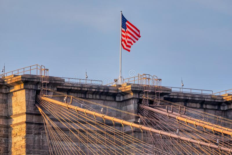 The United States flag on Brooklyn Bridge in New York. The United States flag on center of Brooklyn Bridge in New York stock image