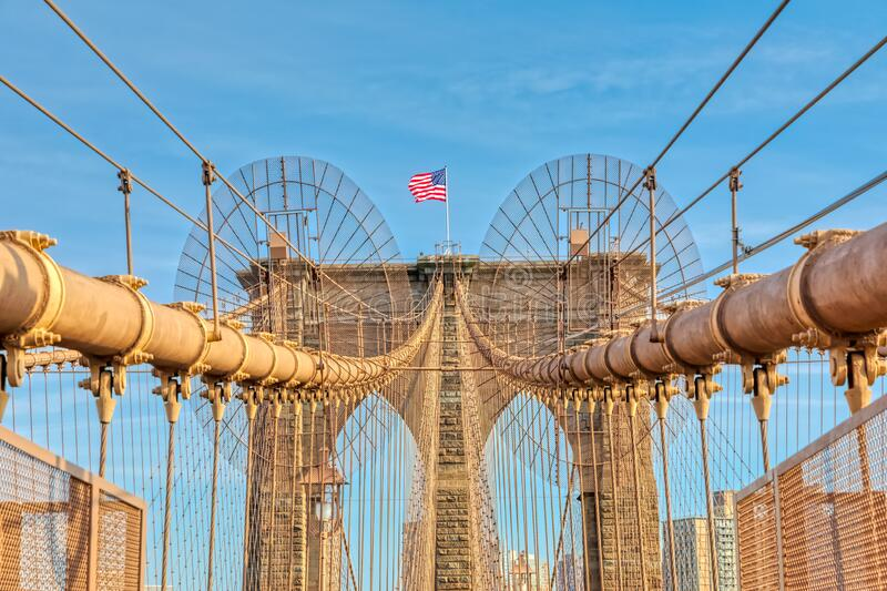 The United States flag on Brooklyn Bridge in New York. The United States flag on center of Brooklyn Bridge construction in New York stock image