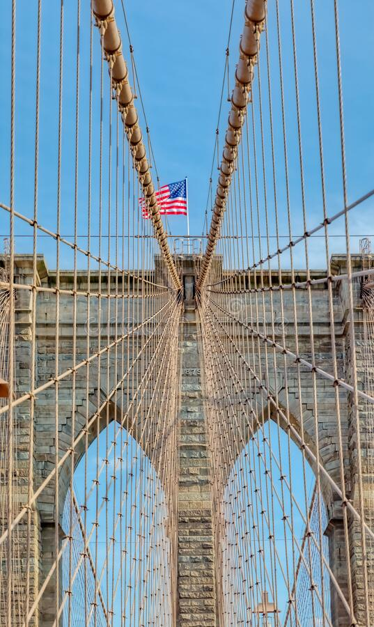 The United States flag on Brooklyn Bridge in New York. The United States flag on center of Brooklyn Bridge in New York, Vertically oriented shot stock photo