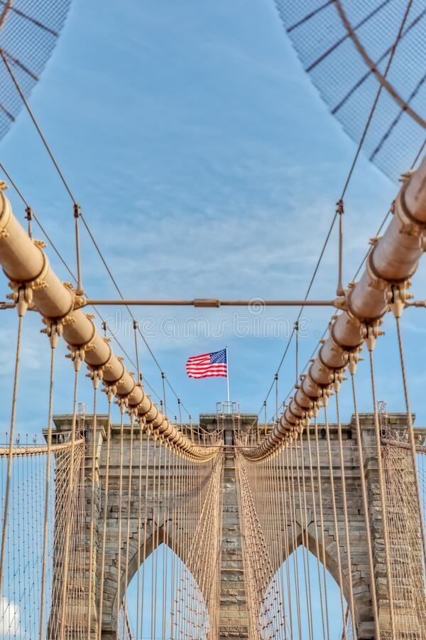 The United States flag on Brooklyn Bridge in New York. The United States flag on center of Brooklyn Bridge in New York, Vertically oriented shot royalty free stock image