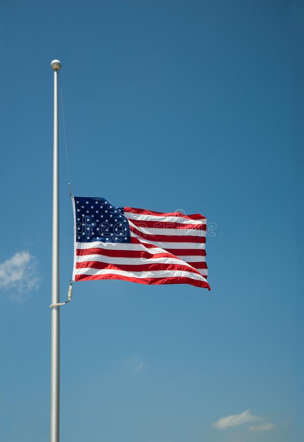 The United States flag flying at half-mast. Or half-staff on a flagpole. Blue sky background with copy space royalty free stock image