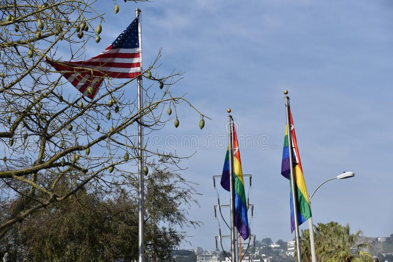 United States and Gay Pride Flags. The United States flag hangs with gay pride flags in West Hollywood Calfornia royalty free stock image