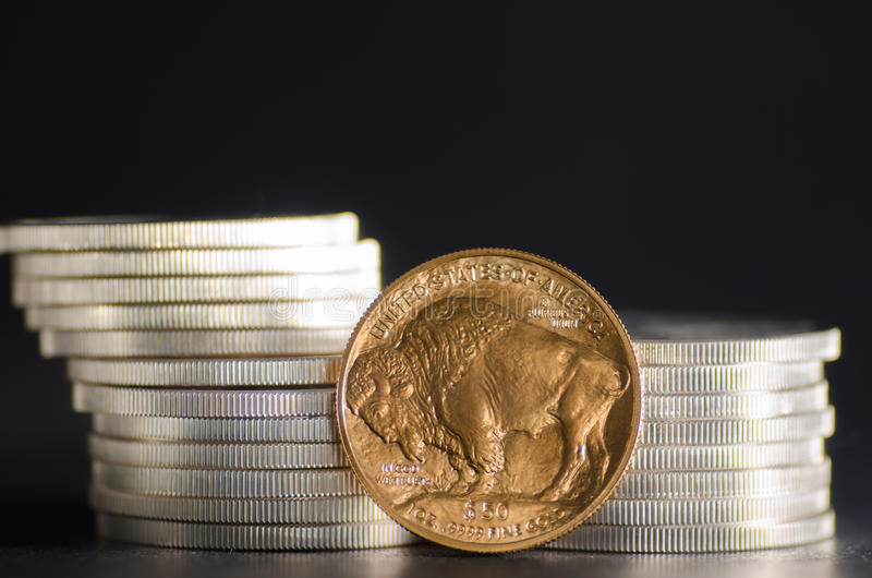 United States Gold Buffalo infront of SIlver Coins. On black background royalty free stock photos