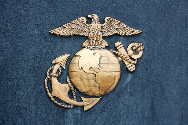 United States Marine Corps Insignia in Gold on Blue. Insignia of the United States Marine Corps in golden burnished metal on a dark blue-gray wall royalty free stock photo