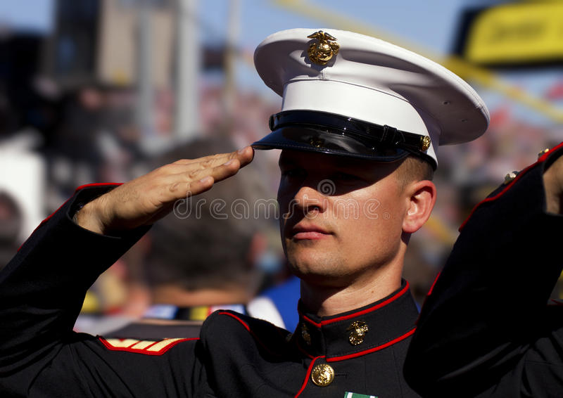 United States Marine Salutes the American Flag. A uniformed United States Marine serviceman salutes the American Flag during the National Anthem stock image