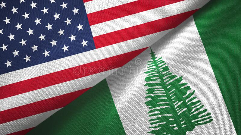 United States and Norfolk Island two flags textile cloth, fabric texture. United States and Norfolk Island two folded flags together royalty free stock images