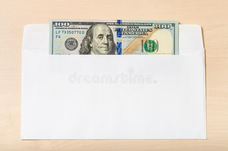 One hundred dollars bill in open envelope on table royalty free stock images