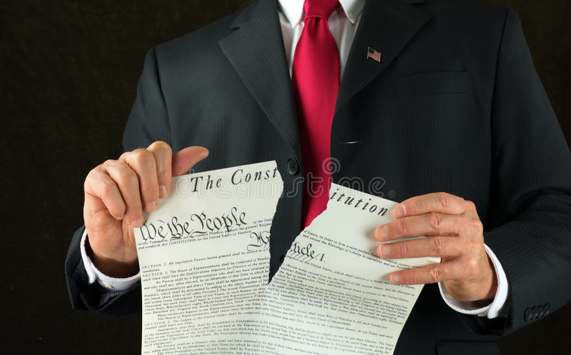 United States politician ripping up and shredding The Constitution representing corruption and injustice. Closeup of politician ripping up & shredding The United stock images