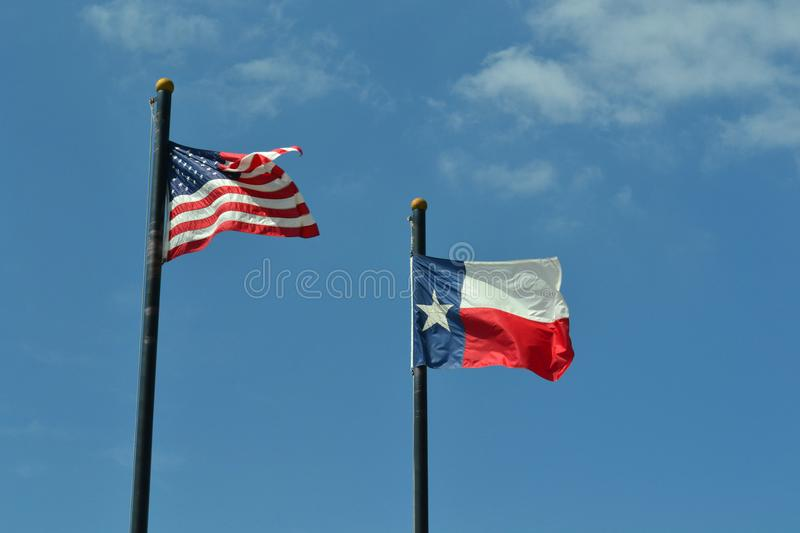 United States and Texas Flags Against Blue Sky. The United States American flag and the Texas state flag against a blue sky with a few clouds. Taken in Jasper stock photography