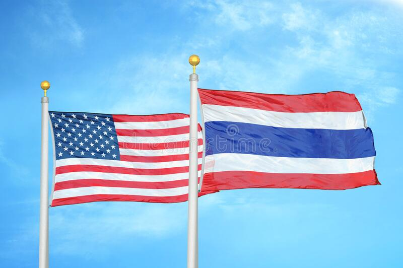 United States and Thailand two flags on flagpoles and blue cloudy sky. Background royalty free stock photos