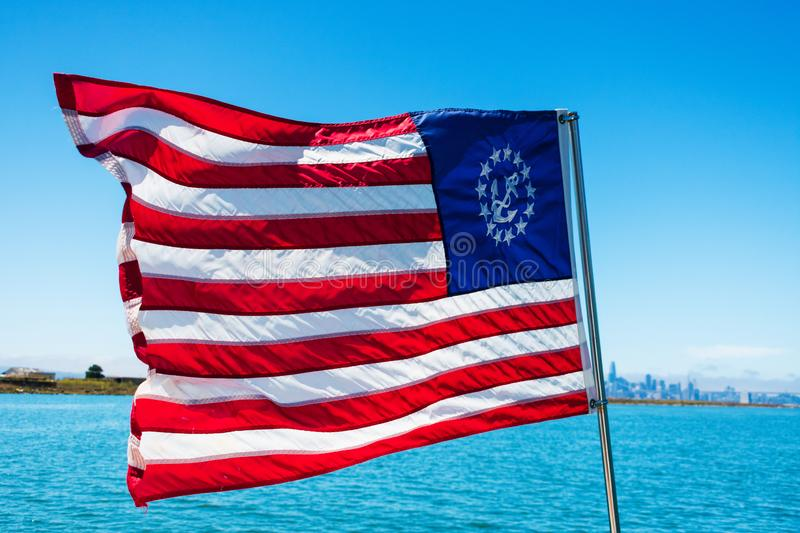 The United States Yacht Ensign. A modification of The United States national flag and ensign with a fouled anchor in a circle of. Thirteen stars in the canton stock images