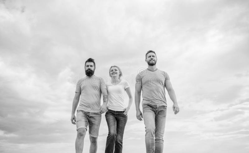 United threesome true friends. Men and woman walks dramatic cloudy sky background. True friendship grow with destiny. United threesome true friends. Men and royalty free stock image