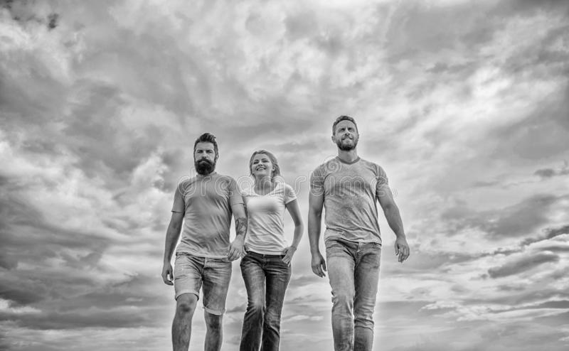 United threesome true friends. Men and woman walks dramatic cloudy sky background. True friendship grow with destiny stock photos