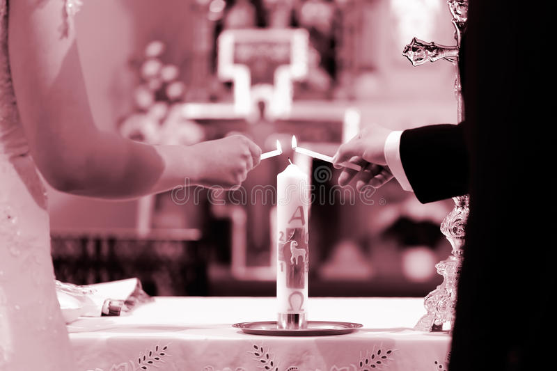 Unity candle ceremony. Bride and groom's hands lighting the unity candle during their wedding ceremony. Colored photo in red royalty free stock image