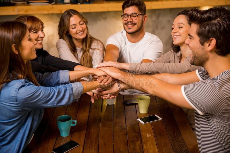 Unity. Group of friends joining their hands together at the cafe royalty free stock photography