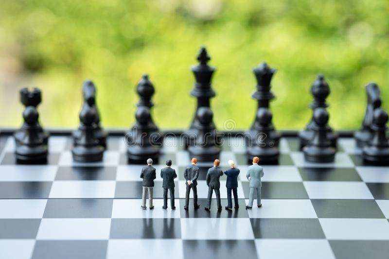 Unity and teamwork in business strategy concept, group of miniature people businessmen collaborate help and work as. Team, standing on chessboard looking at stock image