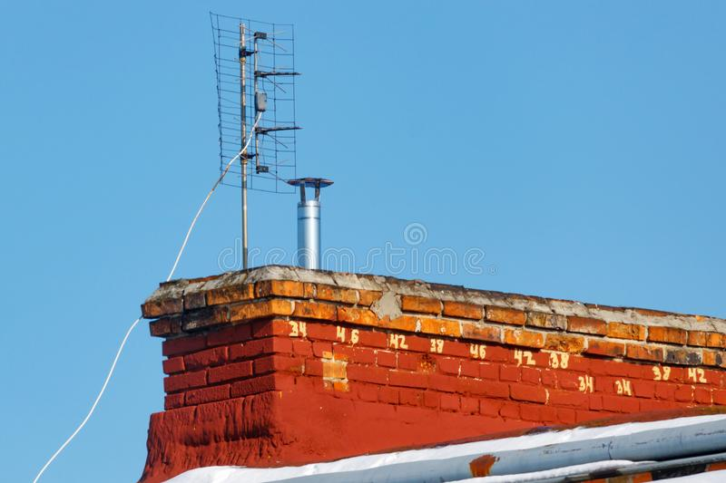 Universal antenna for receiving analog TV signal is installed on the roof of a brick house royalty free stock image
