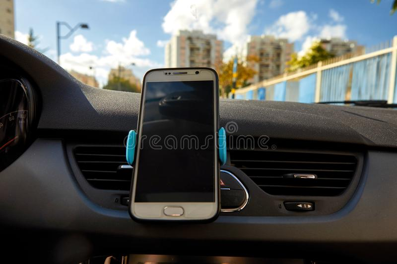 Universal mount holder for smart phones. Car dashboard or wind-shield holder bracket royalty free stock photography