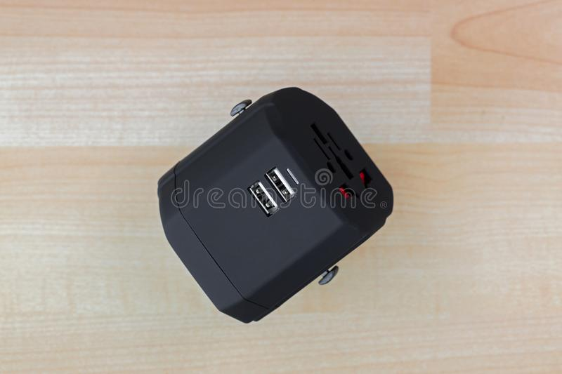 Universal Power Adapter, plug for travel with dual USB ports. All in one travel adaptor. In black on wooden background royalty free stock image