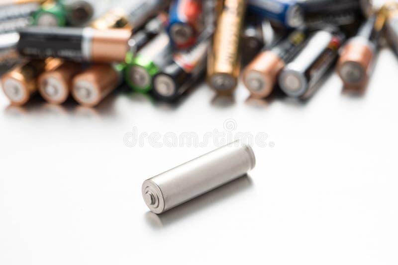 Universellt batteri som jämförs till andra batterier på en vit bakgrund royaltyfria bilder