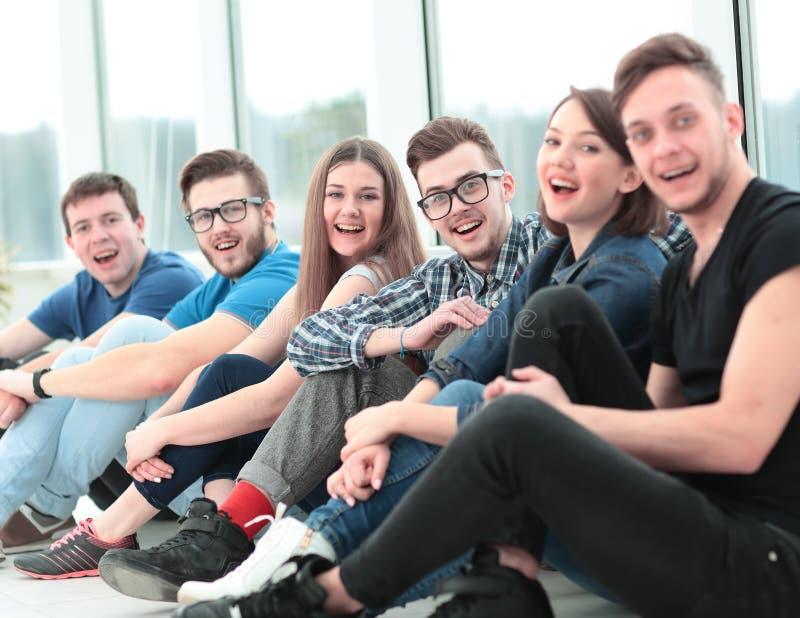 Universidad al grupo de estudiantes que se sientan en el piso en el gimnasio a foto de archivo libre de regalías