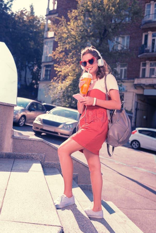 Universidad que entra del estudiante de moda joven con su mochila gris elegante fotografía de archivo