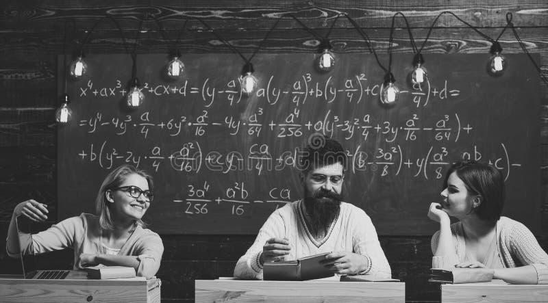 Universidad y concepto de la educación Los estudiantes, los científicos jovenes caen en amor con el fondo de la pizarra del profe foto de archivo