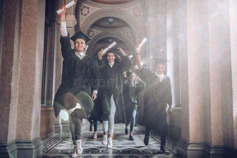 A universidade era os melhores anos de suas vidas! Grupo de estudantes universitário de sorriso que guardam seus diplomas e corre foto de stock