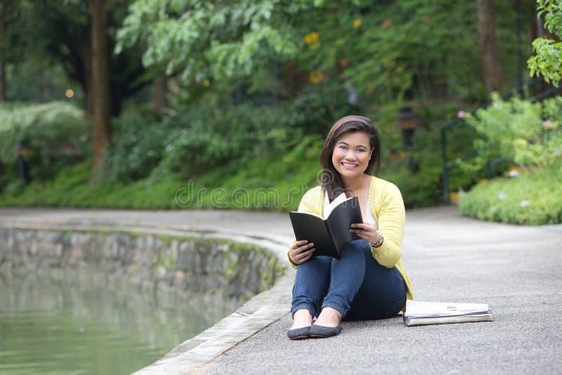 Universidade ou estudante universitário fêmea, assentada por um lago em um parque imagens de stock