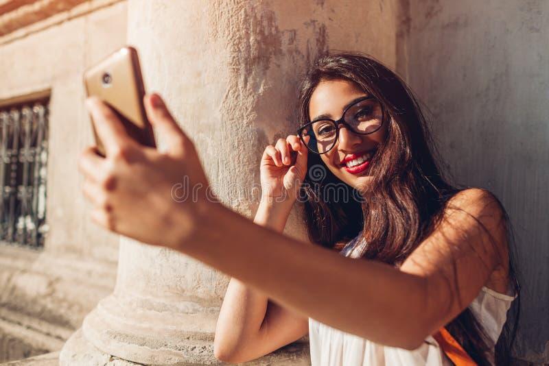 Universitária nova que toma o selfie na rua da cidade Mulher do Oriente Médio feliz que usa o telefone fora fotos de stock
