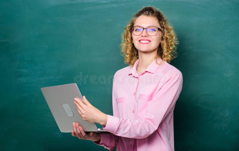 Universitaire student gelukkige student in glazen met laptop leraarsvrouw bij bord E-leert Onderwijs via royalty-vrije stock foto's